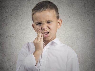 Child toothache. Closeup portrait boy with sensitive tooth ache crown problem touching outside mouth with hand isolated grey wall background. Negative human emotion, facial expression feeling reaction